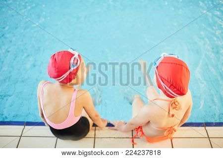 Overview of two girlfriends in swimwear spending time by swimming-pool after school