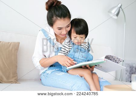 Happy loving family. Pretty young asian mother reading a book to her daughter