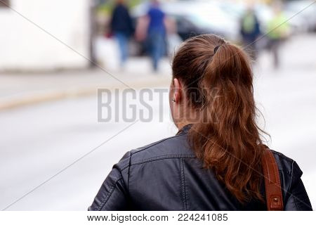 Young woman walking on street. Other people on blurred background. Close up rear view image with space for text.