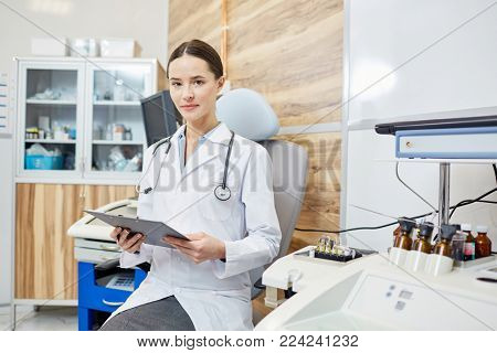 Young female in whitecoat holding medical document while working in hospital
