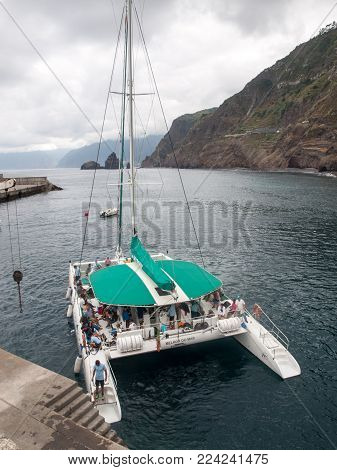 PORTO MONIZ, MADEIRA, PORTUGAL - SEPTEMBER 5, 2016: Catamaran while sailing with tourists docked in Porto Moniz. Madeira, Porttugal