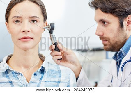 Young professional doctor examining ears of female patient in clinics