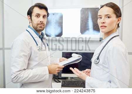 Two young radiologists in uniform looking at camera during work