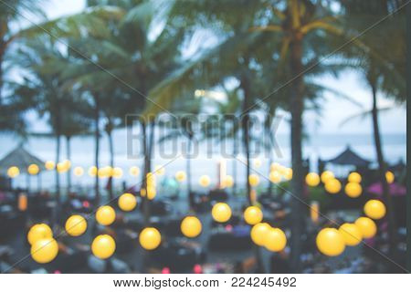 Summer restaurant at late evening in blurred motion. There are some lights in a row with palms above.