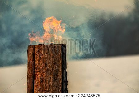 Swedish torch fire burning stub on plate for rest and for warming in winter on the mountain.