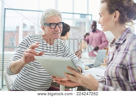 Aged man looking at young manager with touchpad while discussing new curious online information with her