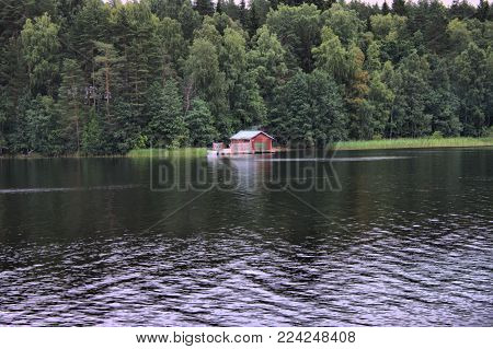 Typical Scandinavian Red Wooden House On The River Of A Lake