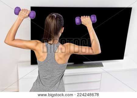 Fitness at home woman working out watching tv. Back of a young sporty girl following workout videos online on flat screen television, lifting weights toning arms exercising strength training.