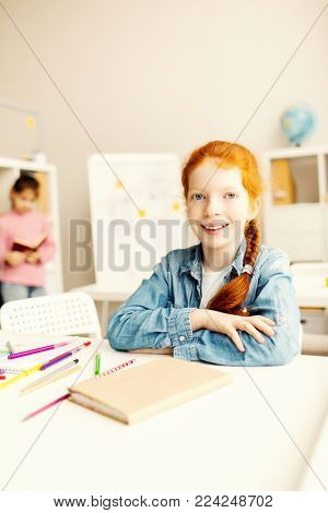 Cheerful and diligent schoolkid sitting by desk in classroom and looking at camera