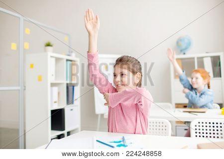 Cute classmates raising their hands while working at lesson