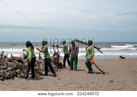Kuta, Bali Indonesia - January 27, 2018 People Collecting Garbage On The Beach. Pollution On The Bea