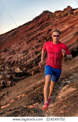 Endurance training fitness man on trail run running outside. Athlete runner in sportswear sunglasses, compression clothes, smart watch.