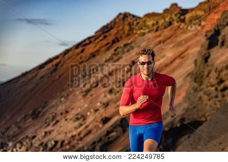 Trail runner on mountain run. Athlete man focused running training endurance. Fitness motivation.