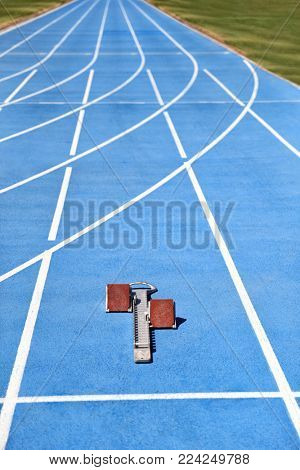 Starting blocks on blue running tracks lanes at track and field. Sport accessory. Vertical crop of stadium floor with copy space background.