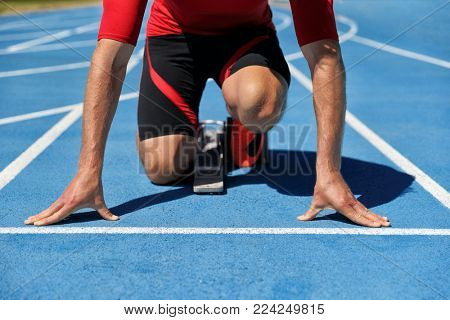Runner athlete starting running at start of run track on blue running tracks at outdoor athletics and fiel stadium. Sport and fitness man lower body, legs and running shoes going sprinting.