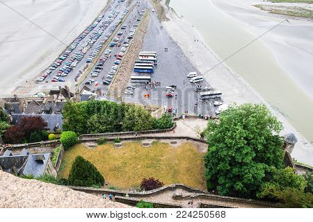 LE MONT SAINT-MICHEL - JULY 5, 2010: above view of car parking and causeway to Saint Michael's Abbey on Le Mont Saint-Michel island in Normandy. Mont Saint-Michel is island commune in Normandy.