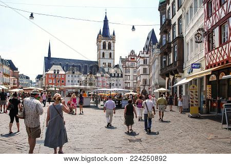 TRIER, GERMANY - JUNE 28, 2010: people walk on Hauptmarkt (Main Market square) and view of St Gangolf Church in Trier city in summer. It is central and one of the largest squares in the city