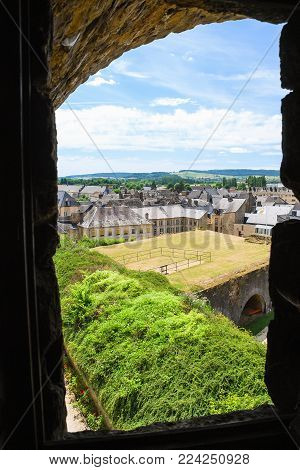 SEDAN, FRANCE - JUNE 30, 2010: view of urban houses through embrasure of castle Chateau de Sedan in summer day. Sedan is a commune in Ardennes department, the castle began to be built in 1424