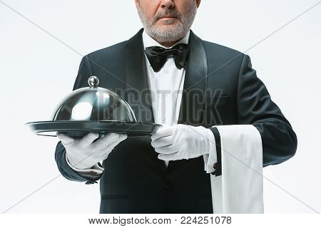 The serious senior waiter holding tray and standing isolated on white studio background. concept of good service at restaurant