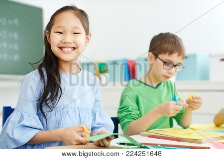 Smiling Asian schoolgirl cutting something from paper sheet at lesson of art and craft