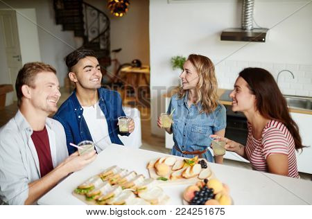 Two guys and their girlfriends holding drinks and enjoying talk at home on Friday evening