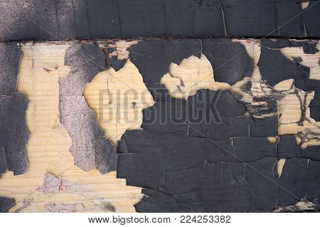 Cracking and peeling black paint on a wall. Vintage wood background with peeling paint. Old board with Irradiated paint