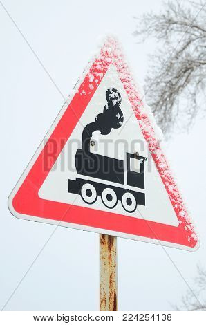 Railway crossing without barrier. A road sign depicting an old black locomotive, located in a red triangle