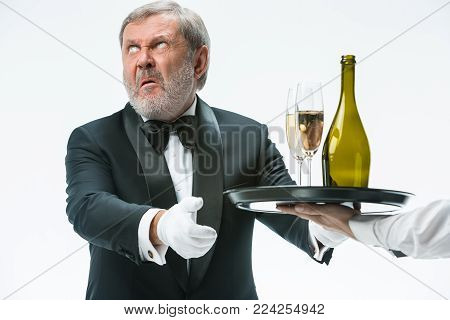 The senior man in suit complaining for the bad wine isolated on white studio background. concept of bad service
