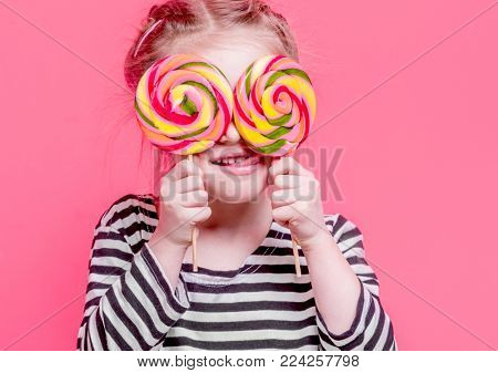 Portrait of litlle girl with lollypops