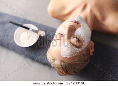 Face mask.Beautiful young girl at spa ,cosmetician woman applying facial mask