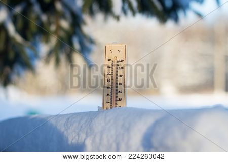 Thermometer in snow in sunny weather. Snowy trees in the background Frosty Day. Winter Concept.