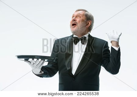 The enthusiastic senior waiter holding tray and standing isolated on white studio background. concept of good service