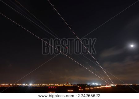 Wide angle view of plane landing and airport lights at night, long exposure with light trail, bottom view