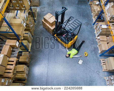 An accident in a warehouse. A man lying on the floor next to a forklift, unconscious. Aerial view.