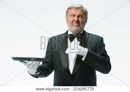 The senior waiter holding tray man with a grimace of disgust on his face and standing isolated on white studio background. concept of bad food poster