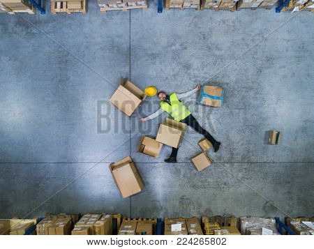 An accident in a warehouse. Man lying on the floor among boxes, unconscious. Aerial view.