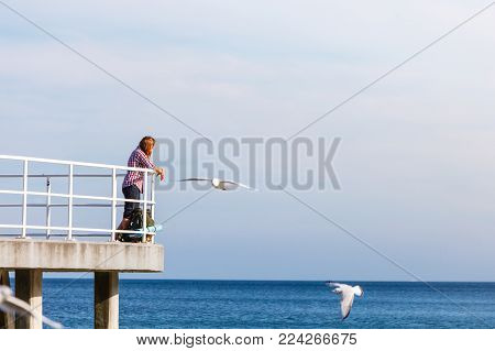 Man hiker backpacker on pier. Young guy tramping with backpack by seaside. Adventure and tourism. Beautiful sea landscape