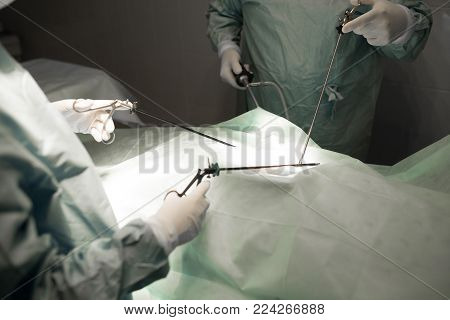 Doctor And Assistance Medical Team Performing Surgery On A Patient In Operation Room. Instruments Fo