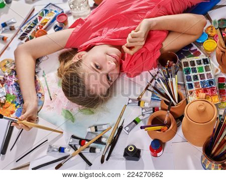 Authentic artist child girl paints lying in creative chaos palette watercolor paints palette and brush . Painting in studio on floor.Top view indoor home interior handmade crafts .