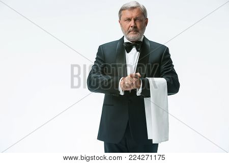 The senior waiter holding white towel and standing isolated on white studio background. sign language in the restaurant. Gesture means - table is not ready
