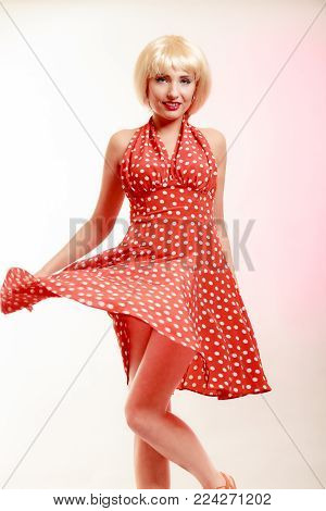Vintage pinup style. Beautiful stylized young woman dancing. Attractive girl in blond wig and retro spotted red dress on pink. Disguise. Party. Studio shot.