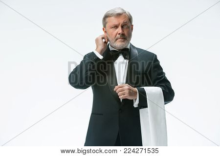 The senior waiter holding white towel and standing isolated on white studio background. sign language in the restaurant. Gesture means - Call me to the phone, I want to get away from this table.