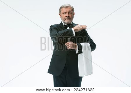 The senior waiter holding white towel and standing isolated on white studio background. sign language in the restaurant. Gesture means - clean the crumbs