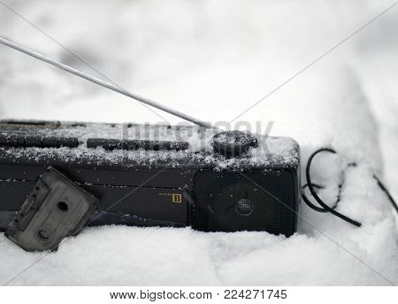 Old cassette player abandoned in the snow, outside closeup shot