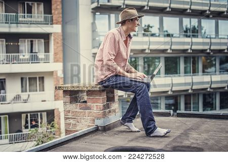 Man in blue jeans and pink shirt sitting on the roof with laptop.