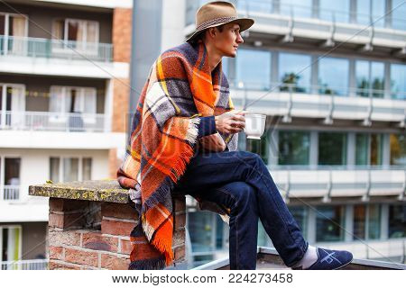 Young man covered with blanket drinking hot tea on the roof.