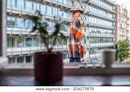 A man covered with blanket standing against city building.