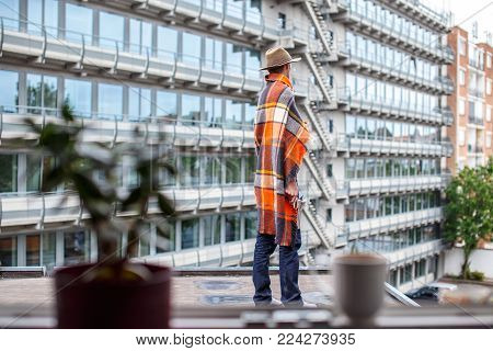 Freezed man covered with blanket on the roof.