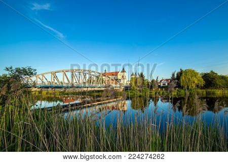 View at bridge over the Narew river and baroque Church of the Holy Trinity in Tykocin town, Podlasie, Poland