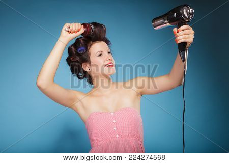 Young woman preparing to party having fun, funny girl styling hair with curlers hairbrush and hairdreyer retro style blue background